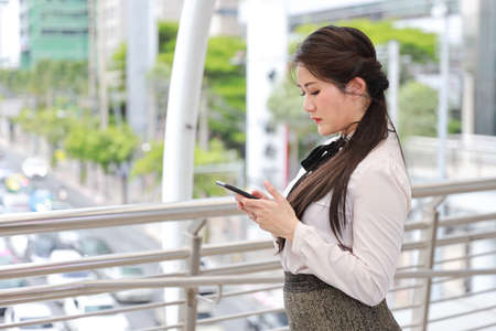 side view successful asian businesswoman in white casual dress who standing on walk way in downtown, she using cell phone with happy smiling face with city background