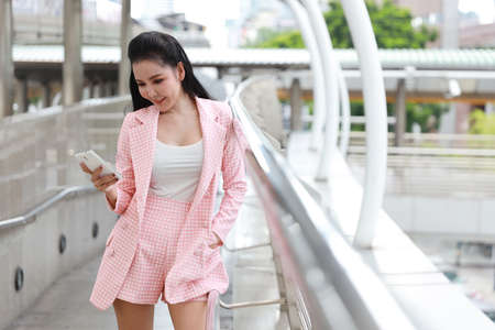 front view successful asian businesswoman in pink casual dress who standing on walk way in downtown, she using cell phone with happy smiling face with city background