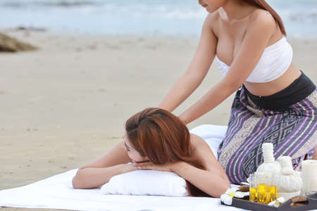 shoulder massage 2 young beautiful and sexy asian women, long hair with white dress enjoying oil spa treatment massage salon, lying on beach in summer holiday vacation. free space for your advertising Stock Photo