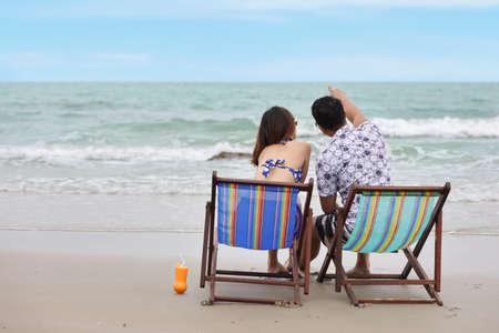 Back view image in love asian couple woman and man who wearing swimming suit sitting and poiting something on deck chair on the beach with orange juice on holiday vacation during happy time in summer