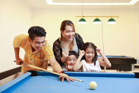 group of happiness asian family father, mother, son and daughter playing billiard or snooker on blue pool table with happy smiling face during holiday vacation Foto de archivo