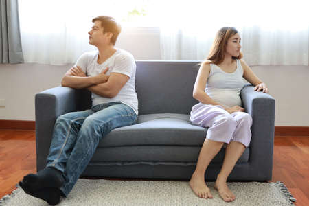 full shot asian pregnant wife and caucasian husband sitting on sofa in living room with angry motion with each other and unhappy face