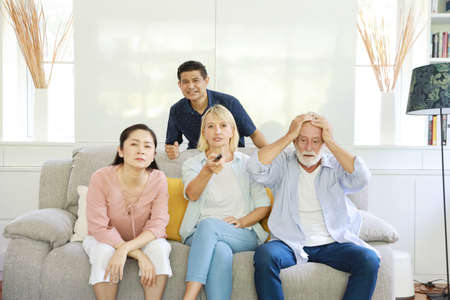 Unhappy elder multiethnic family sitting and watching television on grey sofa in living room. They expressed sadness when the football team they cheered was beaten.