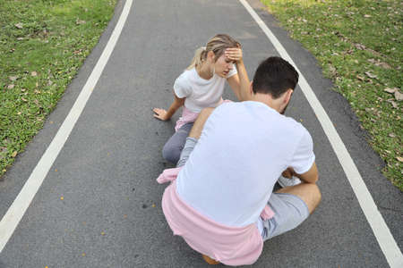 young girl fall down because of the dizziness from too much exercise and young man is helping in the park