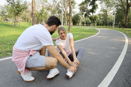 Young caucasian girl fall down because of the dizziness from too much exercise and young caucasian man is helping her in the park. Healthy and sport concept