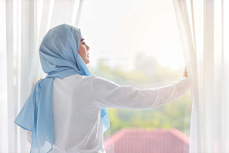 Rear view beautiful asian muslim woman wearing white sleepwear, stretching her arms after getting up in the morning at sunrise. Cute young girl with blue hijab standing and relaxing while looking away Banco de Imagens