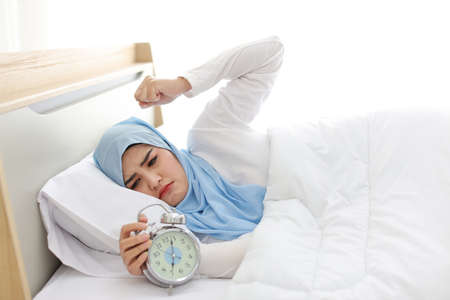 Oversleeping asian muslim woman wearing white sleepwear lying on bed, missing ring of alarm clock waking up. side view portrait young girl trying to stop ringing while her head on pillow Banco de Imagens