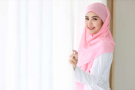 Side view beautiful asian muslim woman wearing white sleepwear, standing at window after getting up in the morning at sunrise. Cute young girl with pink hijab relaxing while looking at camera