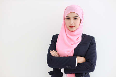 Pretty muslim young asian woman wearing blue suit smiling confident in studio. Isolated white background portrait with beautiful face girl with pink hijab. Advertisement portrait concept. Banque d'images