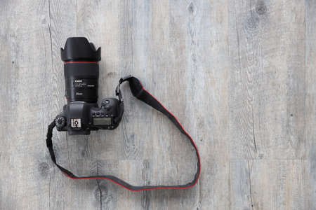 BANGKOK, THAILAND - DEC  21, 2018:. Canon 6D camera with EF 35mm f/1.4L USM lens on wood background Редакционное