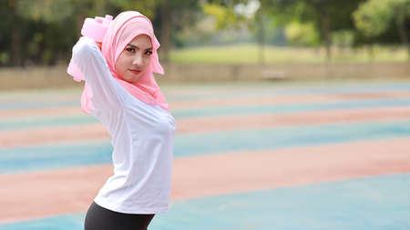 侧视图运动服的运动年轻亚洲回教妇女站立和举哑铃室外为早晨锻炼。