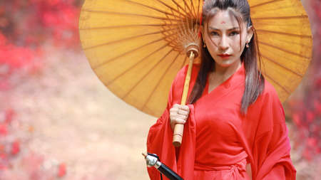 portrait of beautiful asian woman wearing a red warrior Chinese costume with an ancient umbrella and black ancient sword. She standing in nature pink tree with peaceful