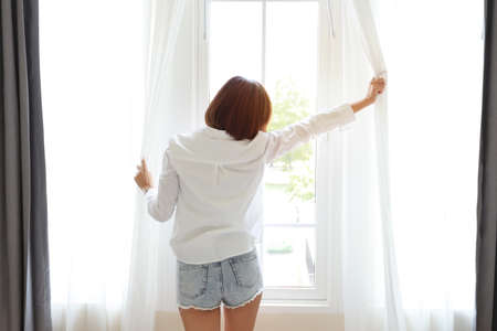 a good shape and healthy asian young woman wake up in the morning at sunrise. She standing and opening curtain at the window in bedroom with happy face after wake up (relaxation concept)
