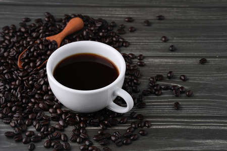 White cup of black coffee with beans and wooden spoon on dark vintage wooden table. Freshness breakfast Americarno with copy space for your advertising content