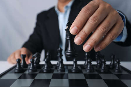 Businessman finger hands with team behind sitting and moving chess king to success position on competition business game, meaning of planning and strategy decision and achievement goal concept. Stok Fotoğraf