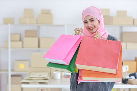 Active pregnant asian muslim woman in casual dress standing and holding shopping bags with online package box delivery background. Beautiful belly girl looking at camera and smile. Pregnancy concept
