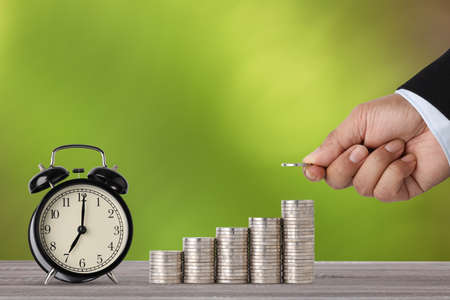 Business investment and saving growth for advertising concept. Businessman hand stacking coin growing with alarm clock on wood table and green nature background, meaning of tax or earning money