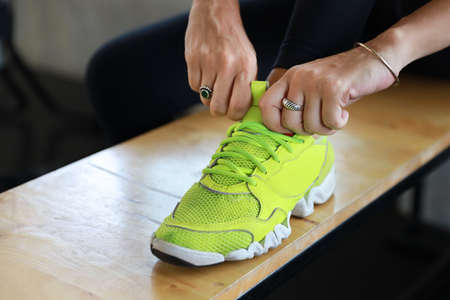 close up image sporty girl hands trying shoelace in gym fitness