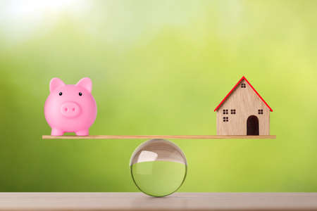 Model house on marble seesaw balancing with piggy bank on green background. Property investment and home mortgage financial real estate advertising concept