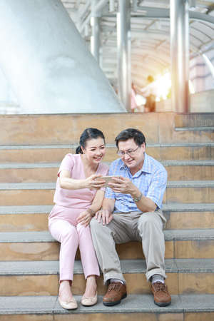 asian traveler couple husband and wife in pink and blue shirt with white nice hat sitting on the stairs in downtown and using cell phone and say hello to someone Stok Fotoğraf