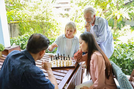 Four multiethnic senior people wearing casual dressed sitting at house, playing chess board and having fun together. Elder caucasian husband man teaching caucasian wife woman how to play. Stok Fotoğraf