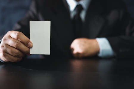 Business man hands in black suit sitting and showing or giving blank business name card while sitting in meeting room.