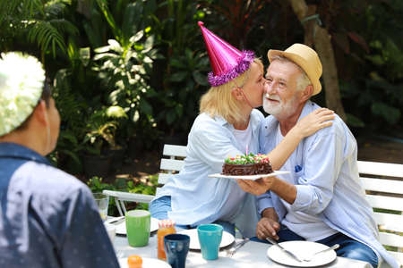 Caucasian elder wife kissing her caucasian husband with happy smiling face on anniversary day while sitting in backyard having breakfast and her husband holding birthday cake Stok Fotoğraf