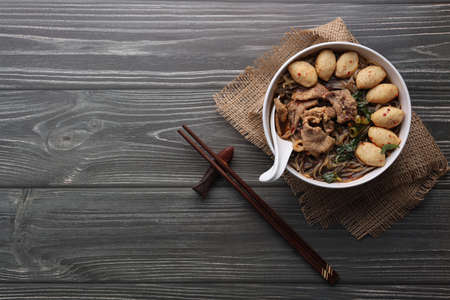 Asian noodles with pork, pork balls, chopsticks and vegetables on dark background. Close up Thai boat noodle culture style top view and flat lay with copy space for your advertising content.