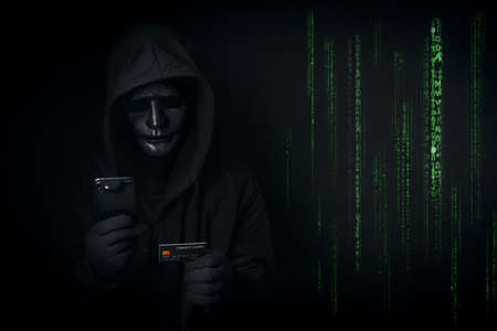 Dangerous anonymous hacker in hooded and mask use smartphone and credit card, break security data and hack password with Bank data account as binary code. Internet crime, cyber attack security concept