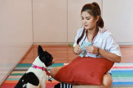 beautiful young asian woman wearing white shirt and holding red pillow who sitting and playing with her cute dog with happy and smiling face in living room. (lifestyle concept) Stok Fotoğraf