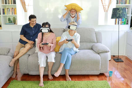 Happy elder multiethnic family sitting on grey sofa in living room and playing game from virtual reality goggles with smiling face