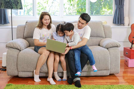 Happy Asian family teaching their children son and daughter how to use computer while sitting on grey sofa in living room with smiling faces