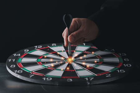 Businessman hand in black suite holding black dart put to center of target board on vintage table meaning of investment and achievement goal. Planning and business strategy concept.