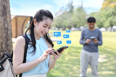 attractive asian woman and man are digital addictive social era by using internet application from cell phone during walking in park outdoor