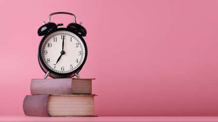Retro alarm clock with vintage books on pink wooden desk in studio using for business or education background with blank copy space for advertising