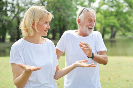 frustrated elderly caucasian wife being comforting by her elderly husband in park outdoor