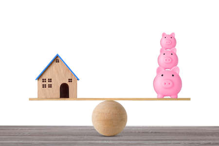 Model house on wooden seesaw balancing with stacking saving piggy bank on white background. Property investment and home mortgage financial real estate advertising concept