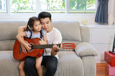happy asian dad teaching his daughter to play acoustic guitar on grey sofa in living room with laughing and smiling face (lifestyle concept)