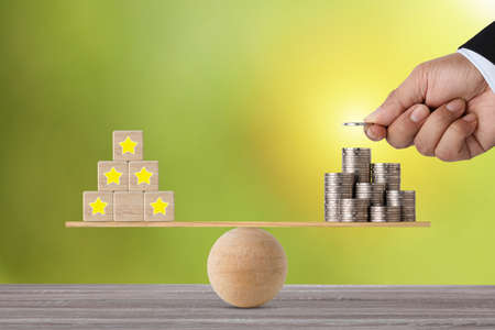 Excellent business five star rating experience on wooden block with businessman client hand putting money on stacking coin on seesaw balancing, meaning business gain money after customer satisfaction