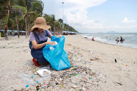 Volunteer tourist with hat is cleaning up garbage and plastic debris on dirty beach by collecting them into big blue bag Stok Fotoğraf