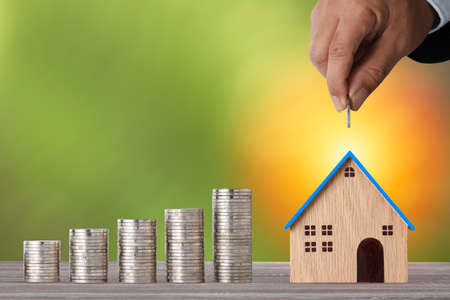 Business property investment with businessman hand putting coin into house model and stacking coins saving growth on wooden desk with green background for financial real estate advertising concept Stok Fotoğraf