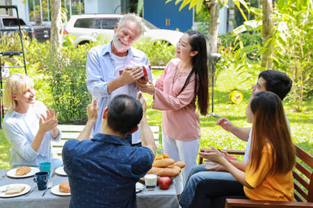Caucasian grandfather got surprise on his birthday from happy multiethnic family with smiling face in backyard outdoor on sunny day