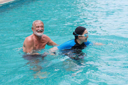 Couple of pensioners seniors in swimming pool having fun and swimming together outdoor in hotel resort, happy and enjoying healthy lifestyle deserved retirement during holiday