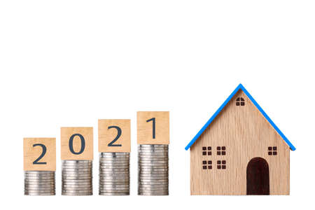 Business investment and saving growth year 2021 for advertising concept. Stacking coin growing with house model on isolated white background studio meaning of financial real estate advertising concept