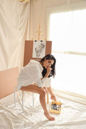full length woman artist in white shirt thinking something while drawing picture with pencil (woman lifestyle concept)