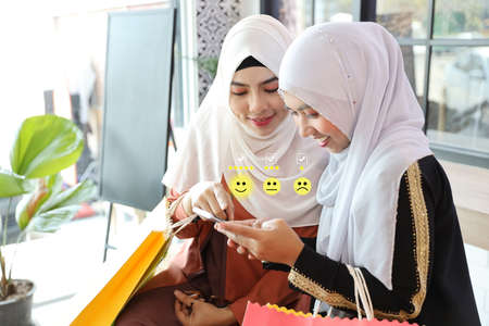 two young attractive muslim women using mobile and pressing smiling face and five stars emoticon on smartphone for evaluation and rating customer service in restaurant