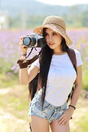 Portrait cute asian photographer girl cover her face with camera. Attractive beautiful traveller women in white shirt and hat with backpack having fun in Asia city outdoor summer time. Stok Fotoğraf