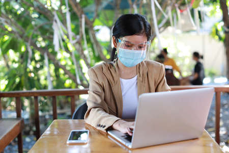 Young asian woman in casual dress with face shield and protect mask for healthcare, sitting in coffee shop and working on computer laptop and smartphone. New normal and social distancing concept Stok Fotoğraf