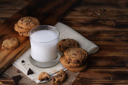 Glass of milk with appetizing delicious sweet homemade chocolate chip on dark vintage wooden table. Tasty dessert for breakfast with copy space for your advertising content