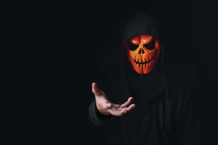 Horror devil costume with spooky pumpkin skull in black dressed for halloween carnival. Devil cosplay in ghost mask and raise hand with blank copy space for your advertising content. Stok Fotoğraf